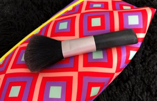 Read on for tips on how to clean makeup brushes. Pictured is a black makeup brush against a bright pink and purple background.