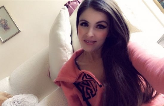 Anne Erickson lounging in a pink Victoria's Secret PINK hoodie.